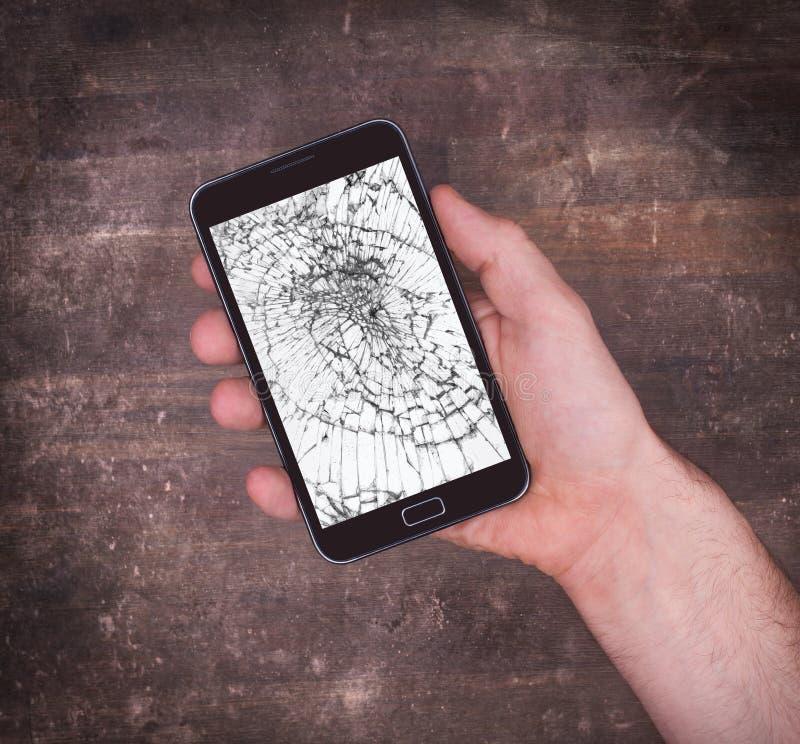 Remettez tenir un téléphone portable avec un écran cassé images libres de droits