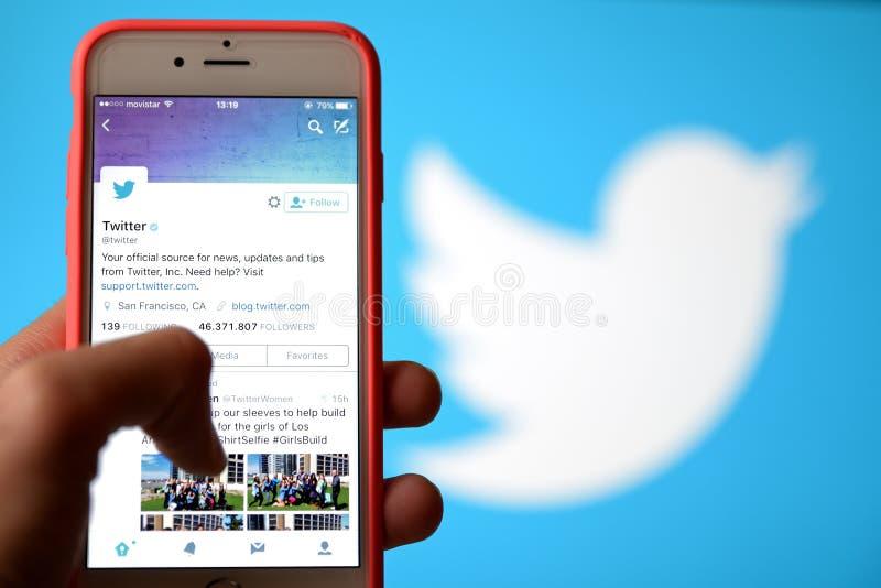 Remettez tenir un téléphone portable et employer le Twitter social de réseau images libres de droits