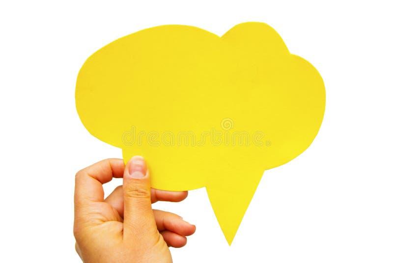 Remettez tenir une bulle jaune vide de la parole de papier de main-cuted sur le fond blanc D'isolement image libre de droits