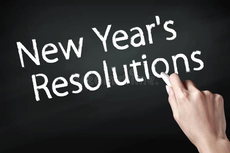 Remettez tenir une craie et écrire des résolutions de nouvelle année photographie stock libre de droits
