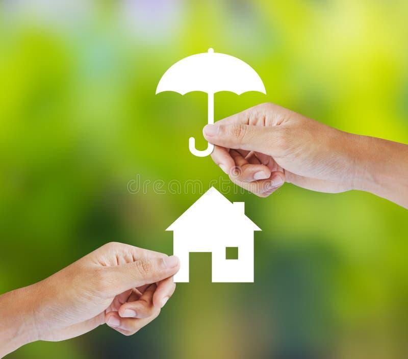 Remettez tenir une maison et un parapluie de papier sur le fond vert image libre de droits