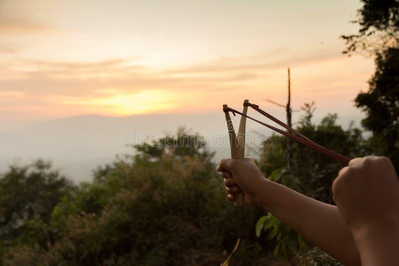 Remettez tirer la fronde préparant au tir pendant le temps de coucher du soleil image stock
