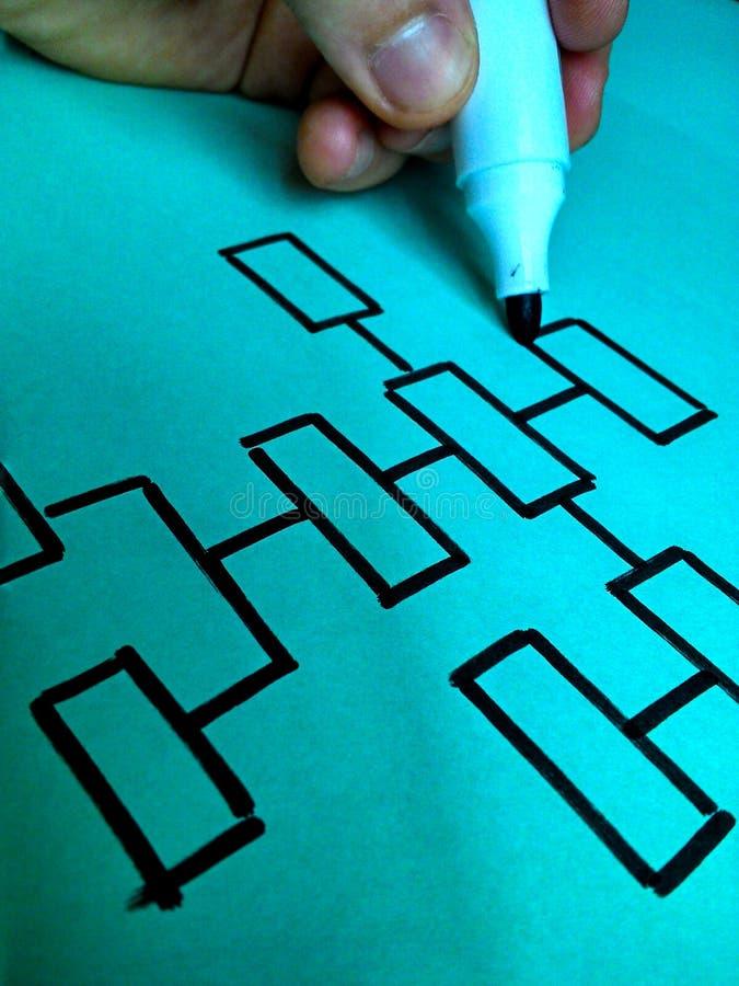 Remettez tracer un organigramme sur un papier bleu avec un stylo photographie stock libre de droits