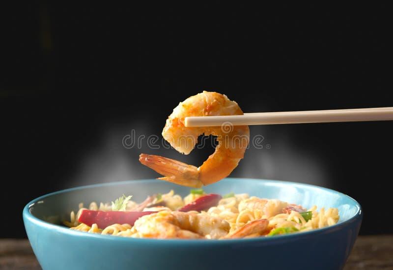 Remettez utilisant la crevette de collecte de baguettes avec les nouilles instantanées avec le SM photo stock