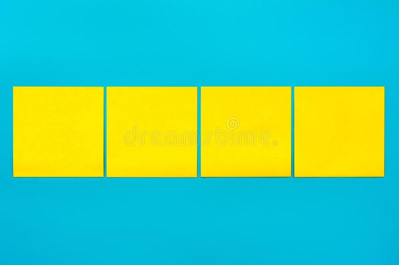 Reminder and combination concept- Close up four yellow empty square stickers on blue background with copy spase, mock up. Horizontal orientation, note, message royalty free stock image