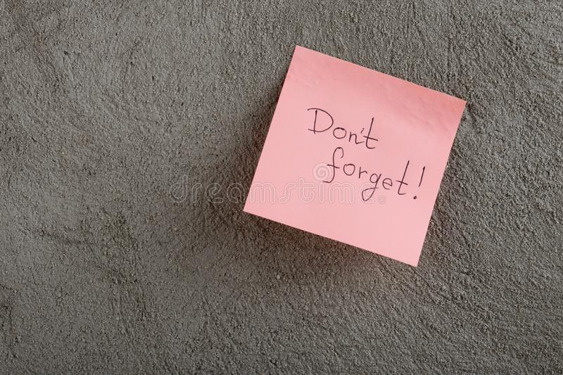 A reminder - don't forget written on color sticker notes on cement background. Sticky, dont, memo, message, office, paper, post, board, information stock photography
