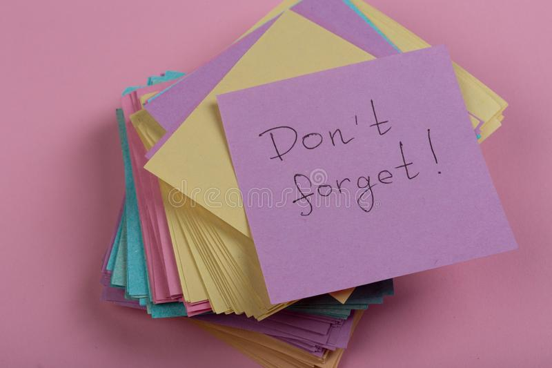a reminder - don't forget written on color sticker notes on pink background stock image