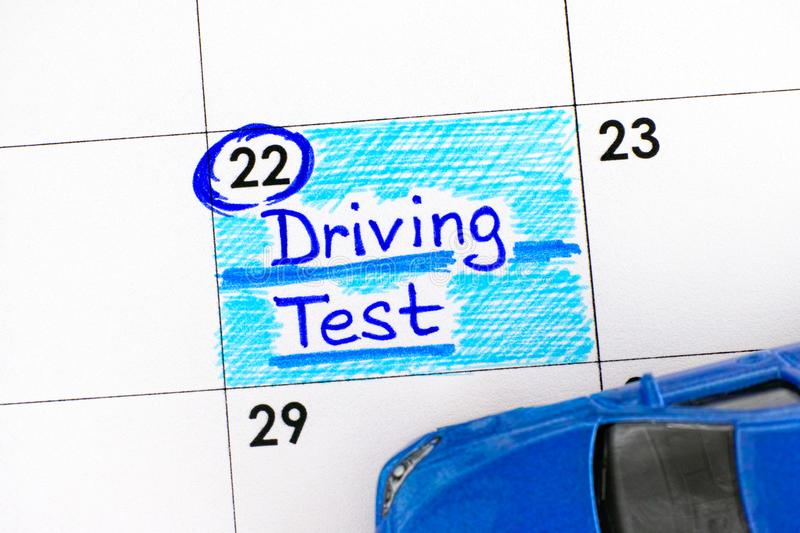 Reminder Driving Test in calendar with blue toy car. Close-up stock images
