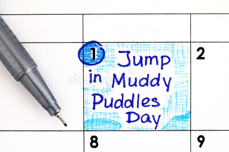 Reminder Jump in Muddy Puddles Day in calendar with pen. April 01 stock photos