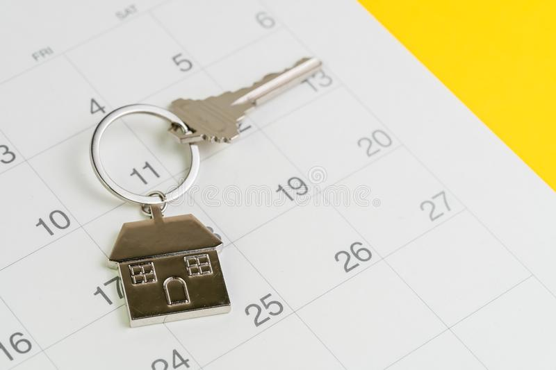 Reminder to pay for mortgage, schedule event or real estate payment day, silver house keyring on white clean calendar, yellow. Background royalty free stock photography