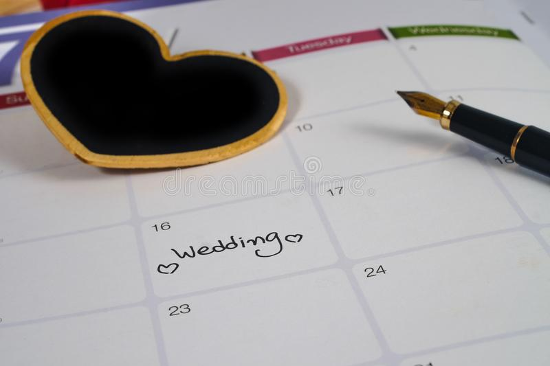Reminder Wedding day in calendar planning with black heart sign and fountain pen. Reminder Wedding day in calendar planning with black heart sign and fountain stock image