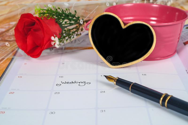 Reminder Wedding day in calendar planning with black heart sign and fountain pen. Reminder Wedding day in calendar planning with black heart sign and fountain royalty free stock photography