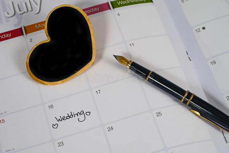 Reminder Wedding day in calendar planning with heart sign and fountain pen. Reminder Wedding day in calendar planning with black heart sign and fountain pen stock image