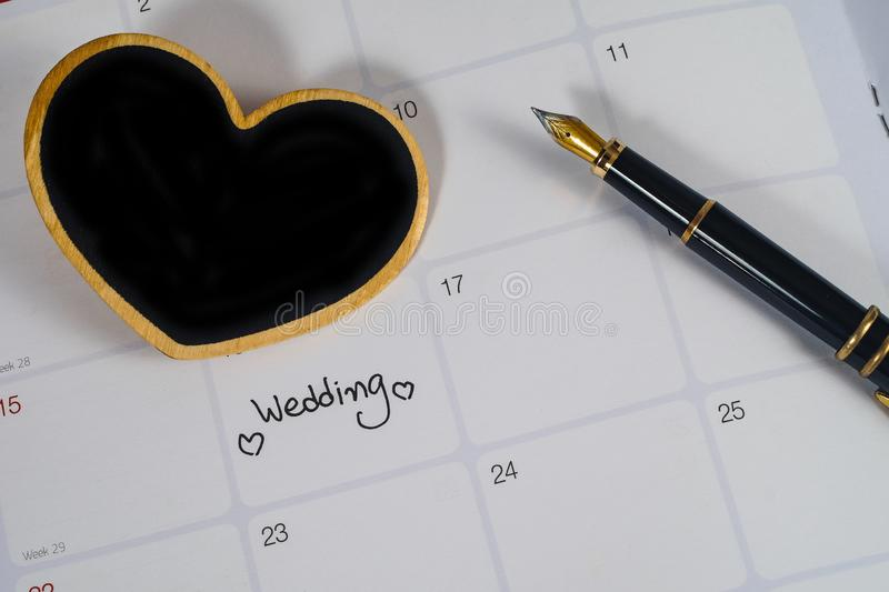 Reminder Wedding day in calendar planning with heart sign and fountain pen. Reminder Wedding day in calendar planning with black heart sign and fountain pen royalty free stock photography