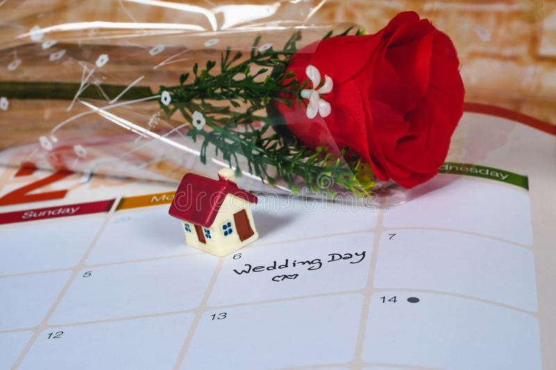 Reminder Wedding day in calendar planning and house. Reminder Wedding day in calendar planning and mini house stock images