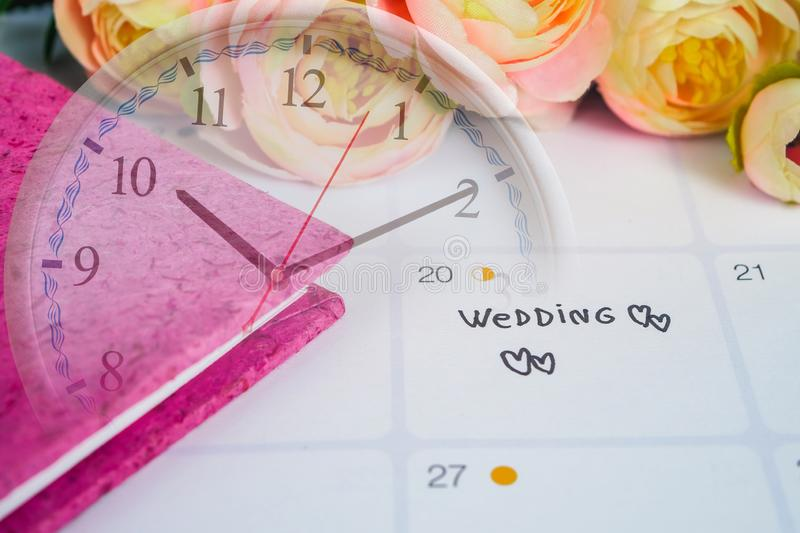 Reminder Wedding day in calendar planning. And pen with clock stock image