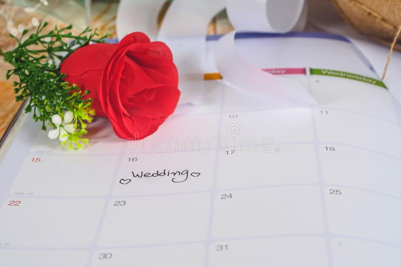 Reminder Wedding day in calendar planning with rose. Reminder Wedding day in calendar planning with red rose stock photo
