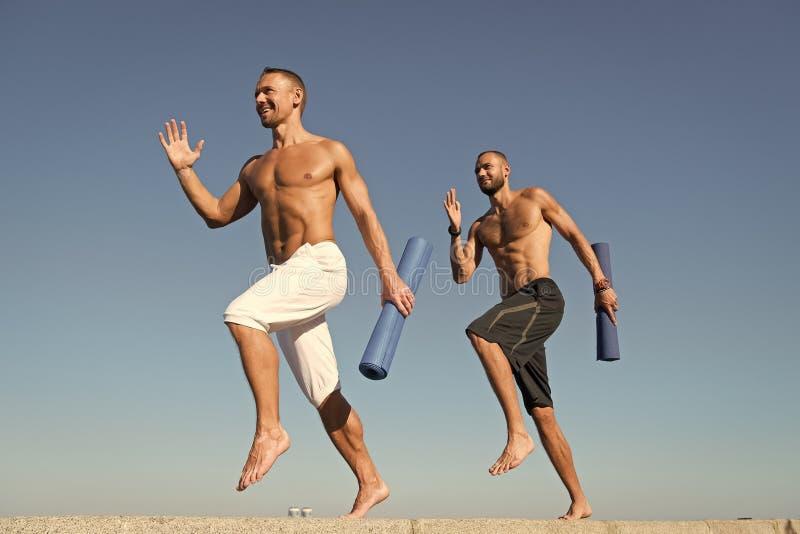 Remita a la forma de vida sana Hombres con la estera de la yoga capturada en fondo del cielo azul del movimiento Deportista con e foto de archivo libre de regalías