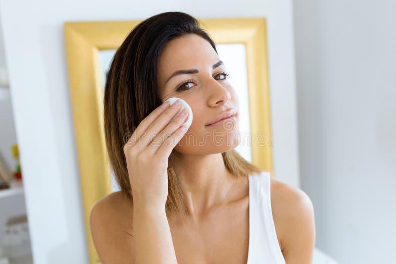 A remoção bonita da jovem mulher compõe na frente do espelho no banheiro fotos de stock