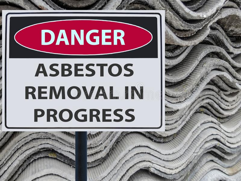 Remoção de asbesto do perigo do sinal em andamento e uma pilha de telhado das folhas do asbesto imagem de stock royalty free