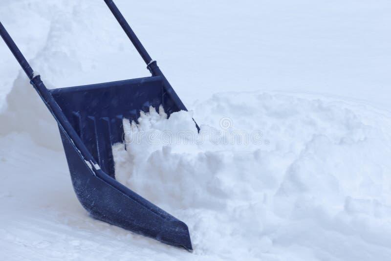 Remoção de neve manual com a colher da neve após o blizzard foto de stock