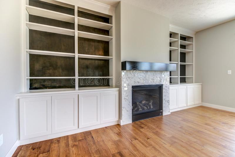 Remodel of some built-in shelving around a fireplace. White shelves, contemporary fireplace, hardwood floors royalty free stock image