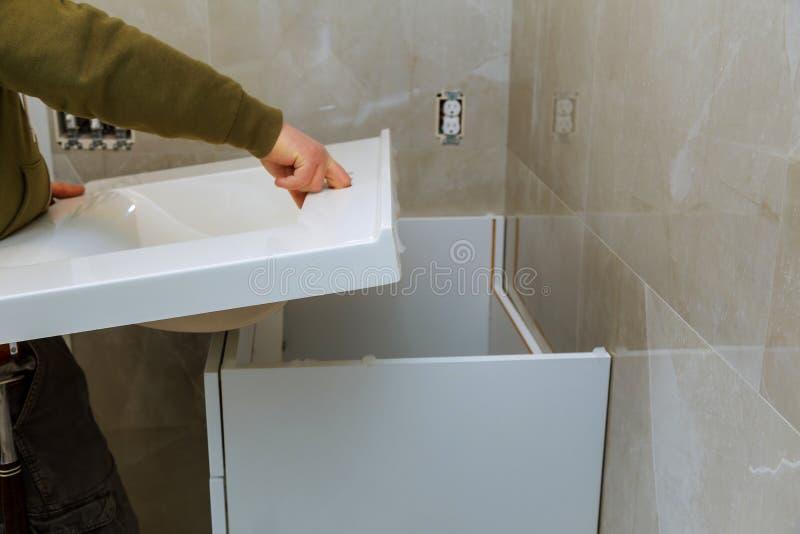 Remodelando a renovação no banheiro com instalação da torneira contrária imagens de stock