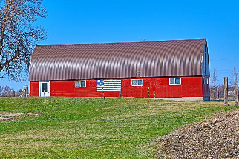 Remodeled Red Wood Barn with a Flag stock photos