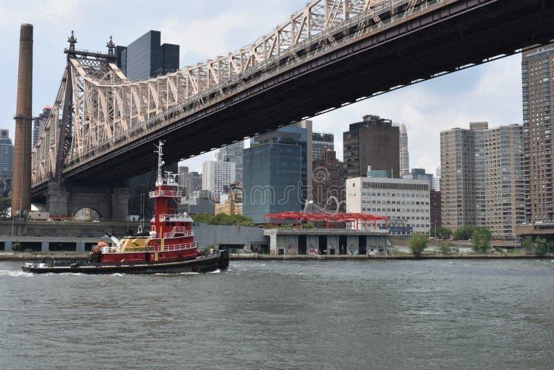 Remolcador debajo del puente en Nueva York fotografía de archivo