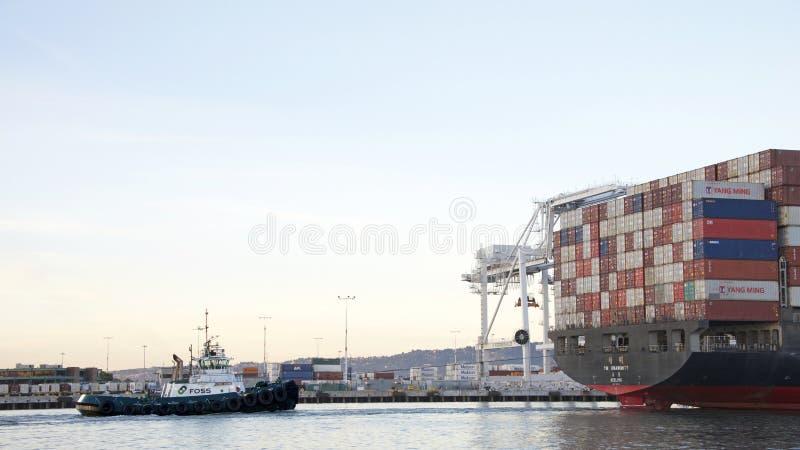 Remolcador LYNN MARIE en la popa de la UNANIMIDAD del buque de carga YM fotos de archivo
