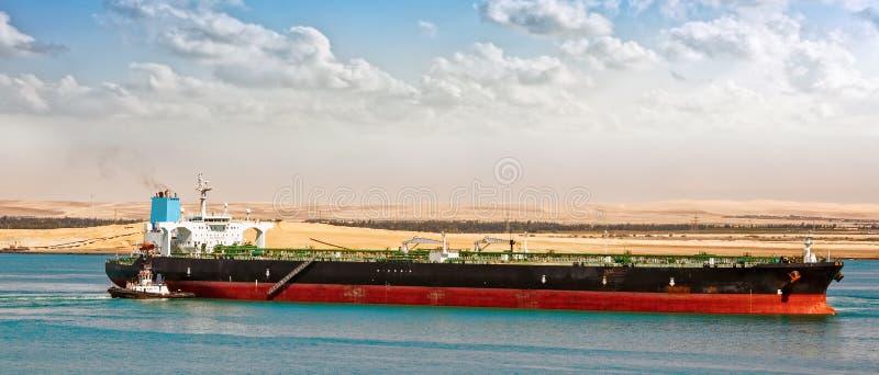 Remolcador que ayuda al petrolero gigante imagenes de archivo