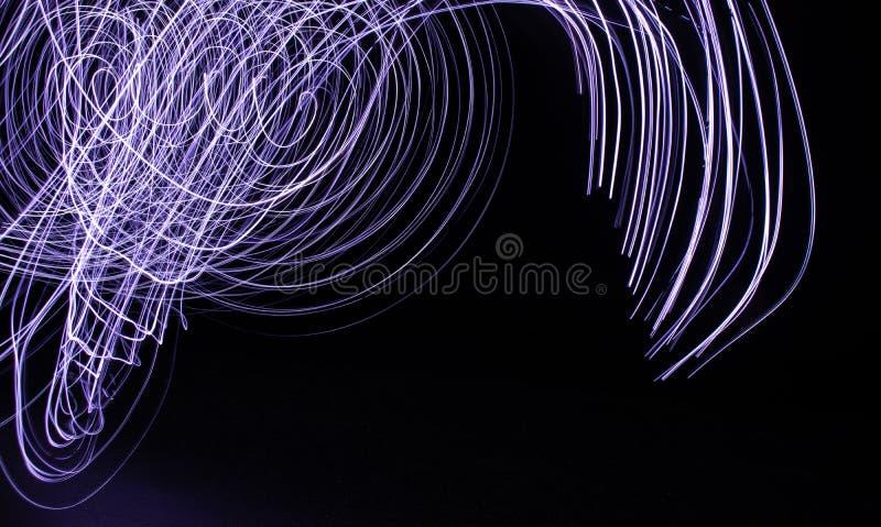 Remolino de luces azules y blancas contra fondo negro fotografía de archivo libre de regalías