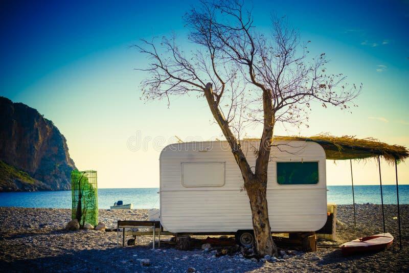 Remolque de la caravana en la playa soleada foto de archivo