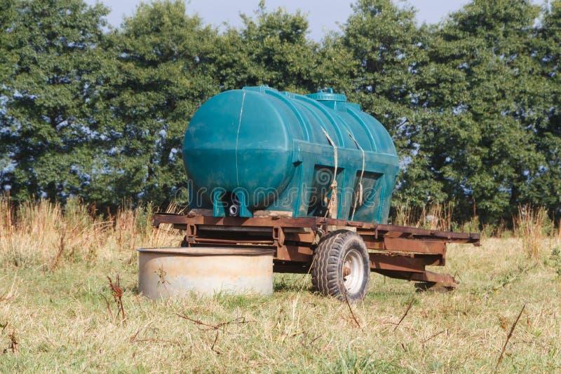 Remolque del tanque de agua para el ganado en un campo foto de archivo