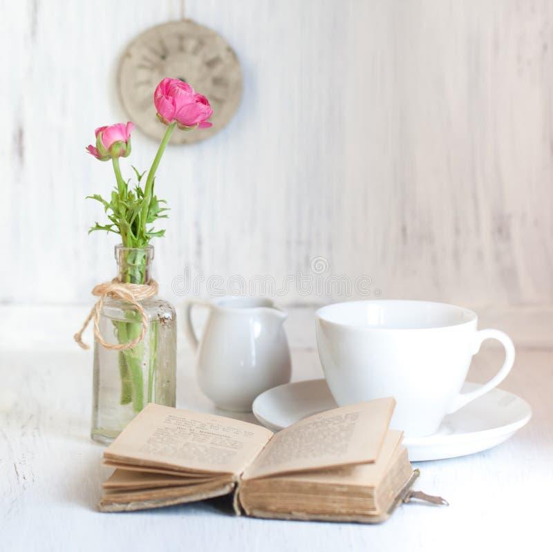 Remolque el ranúnculo rosado de las flores y el libro viejo de la apertura imagen de archivo