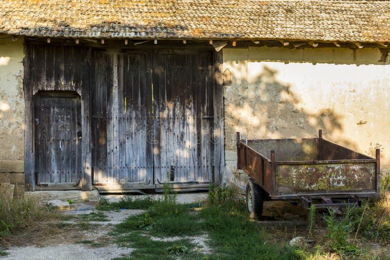Remolque viejo y oxidado delante de una granja abandonada imagenes de archivo