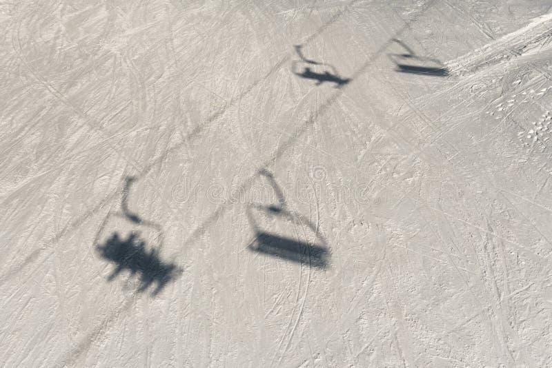 Remonte-pente de chaise avec des silhouettes de skieurs dans l'ombre profonde de mistSilhouette d'un remonte-pente de chaise, sur photos stock