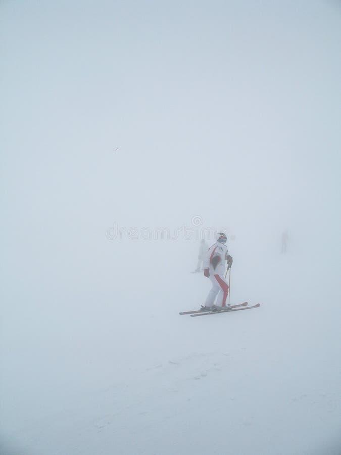 Remonte-pente glacial avec le skieur inexpérimenté dedans en brouillard épais Skieurs dans le brouillard sur une montagne neigeus image libre de droits