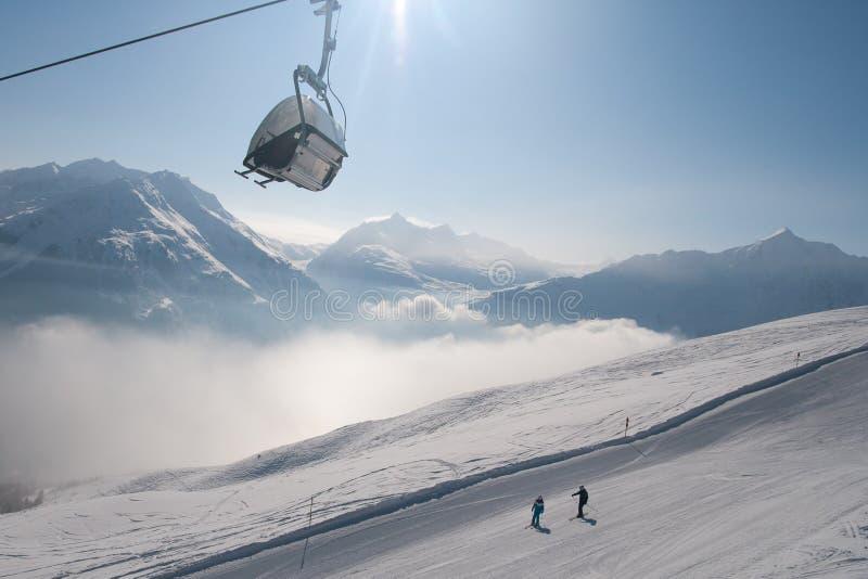 Remonte y esquiadores foto de archivo