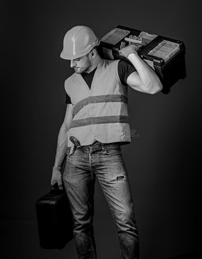 Remontowej usługa pojęcie Mężczyzna w hełmie, ciężki kapelusz trzyma toolbox i walizkę z narzędziami, błękitny tło Pracownik, nap obrazy royalty free