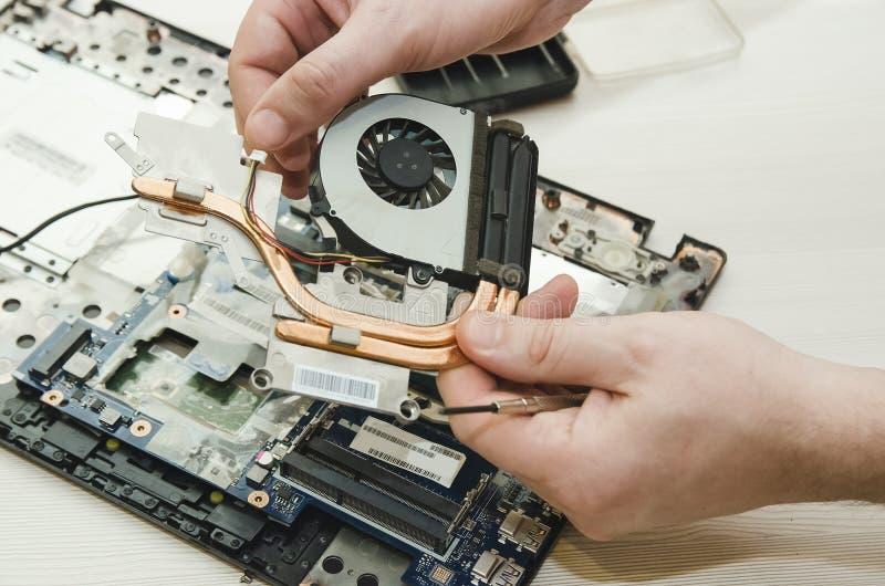 Remontowi laptopy ręki i rozmontowywający stary komputer, zdjęcia stock