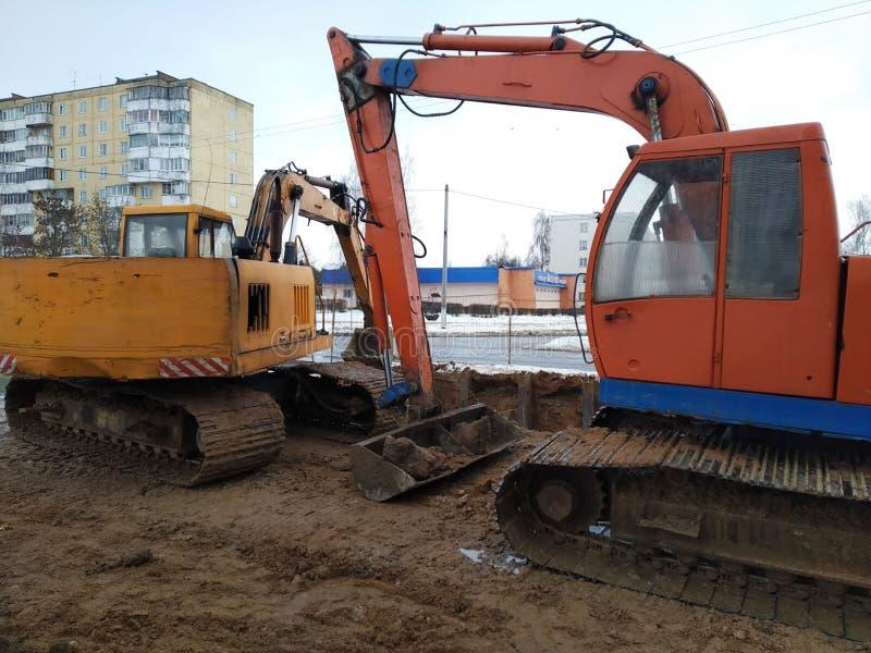 Remontowi robot budowlany hydrauliczny ekskawator na gąsienicie kurs pomarańcze i żółty kolor, szaniec w mieście obraz stock