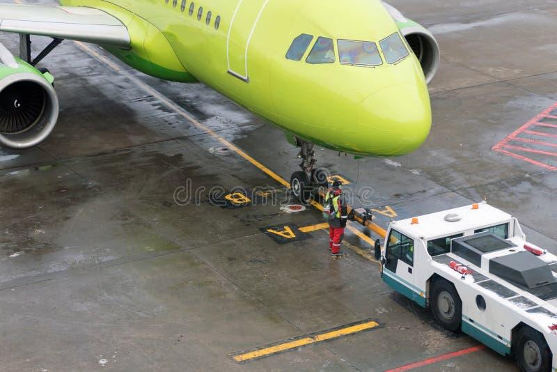 Remorquage des avions de la piste au parking à l'aide de l'équipement spécial photographie stock
