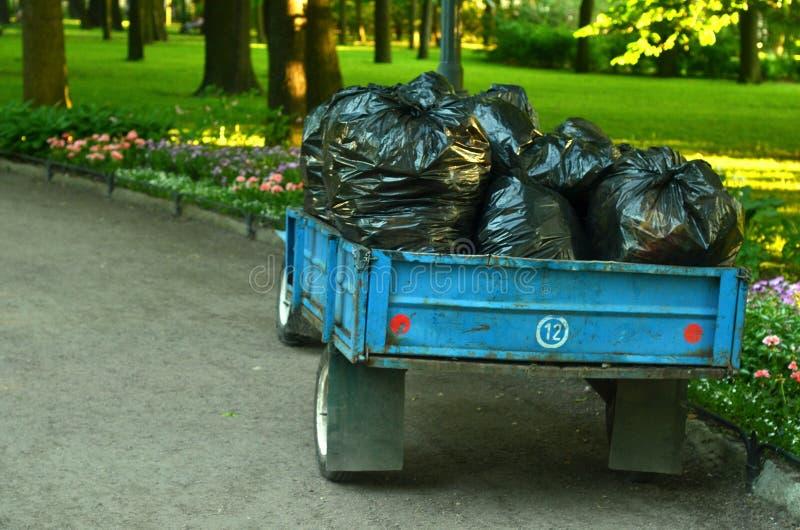 Remorque avec beaucoup de sacs des déchets d'usine dans le jardin Récupération de place périodique photographie stock libre de droits
