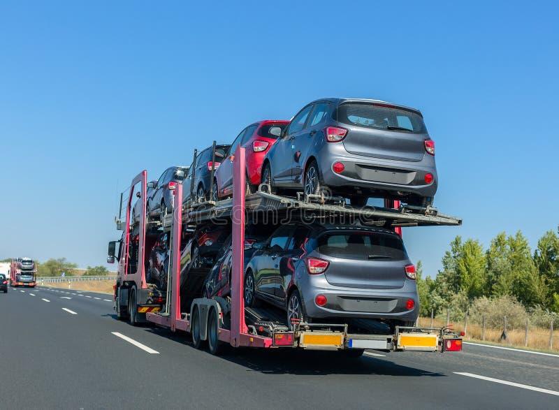 remorque de transporteur de voiture avec des voitures sur la plate forme de couchette camion de. Black Bedroom Furniture Sets. Home Design Ideas
