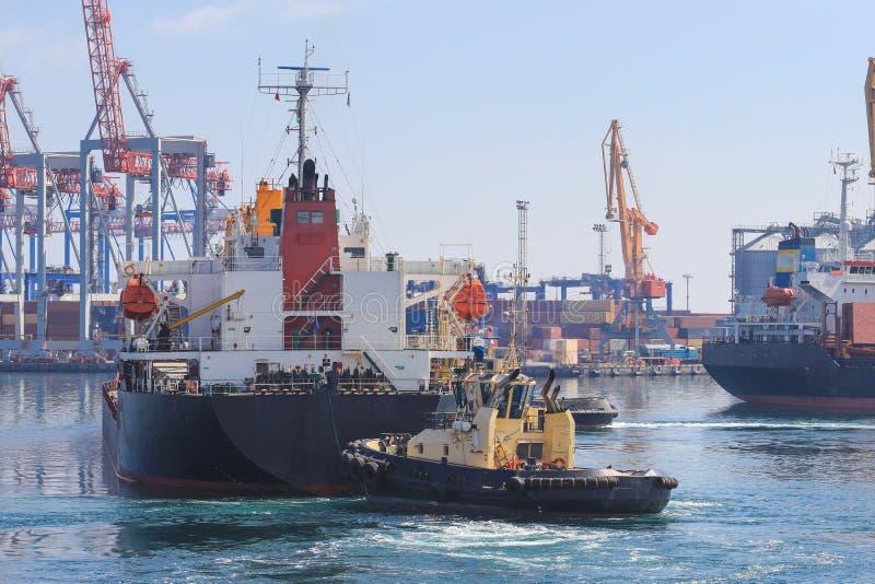 Remorqueur à l'arc du cargo, aidant le navire pour manoeuvrer dans le port maritime photos libres de droits