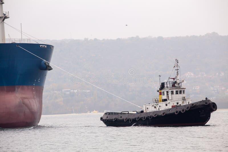 Remorqueur aidant le navire énorme photographie stock
