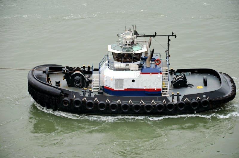 Remorqueur assistant l'amarrage à quai du navire de charge, baie de New York photos libres de droits