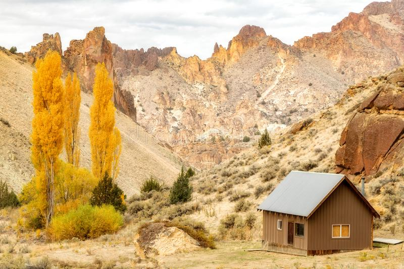 Remote cabin in an Oregon canyon with yellow fall trees and moun. Cabin on land in a deep canyon with autumn trees and cliffs in Oregon wilderness stock photo