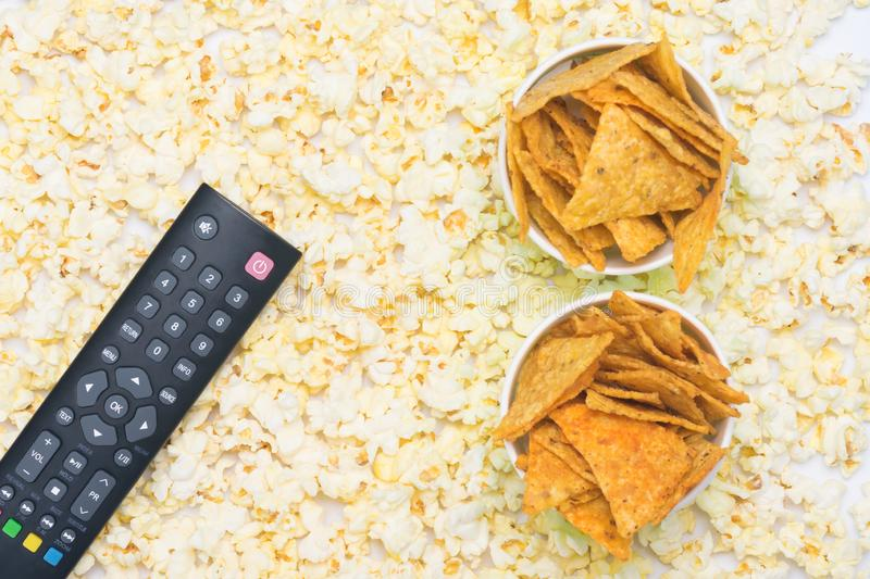 The remote control with buttons lies on popcorn with two paper cups filled with nachos stock photo